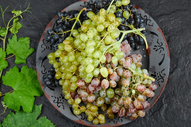 暗い背景のブドウの葉の周りの混合ブドウのプレートの上面図。高品質の写真