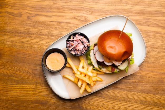 Вид сверху на тарелку с гамбургером, картофелем и соусом.