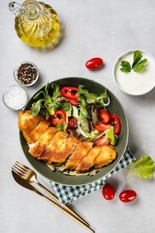 Вид сверху на тарелку с запеченным филе трески с салатом
