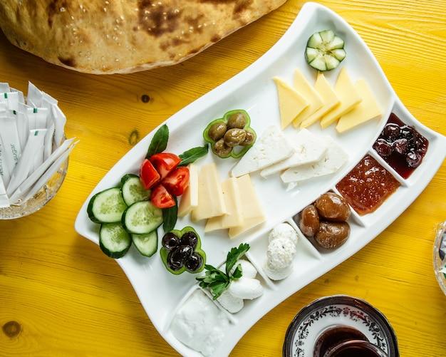 Вид сверху тарелки с завтраком со свежими овощами, оливками, сыром, медом и джемом, подается с чаем