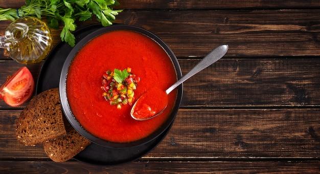 生トマトとコピースペースを持つ野菜で作られた夏の冷たいガスパチョスーププレートの平面図です。