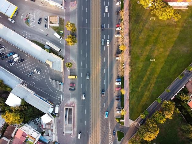 ブカレストの道路の上面図、複数の車、駐車場、右側の緑の芝生、ドローン、ルーマニアからの眺め