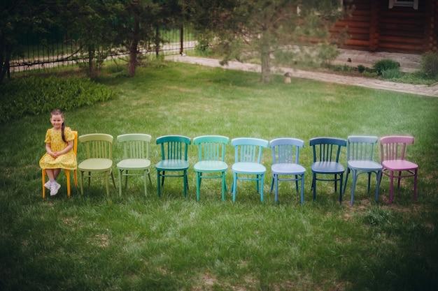 공원의 푸른 잔디밭에서 결혼식을 위한 다채로운 나무 의자 줄의 꼭대기 전망