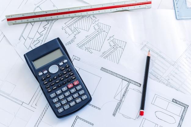 Вид сверху научного калькулятора на строительных чертежах и инструментах для эскизов