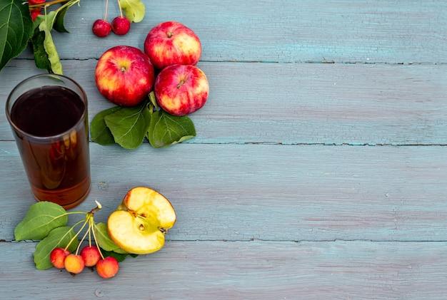 あなたのテキスト、コピースペースのための場所と青い木製の背景の上のガラスの庭のリンゴとリンゴジュースの新鮮な収穫の季節の静物の上面図。