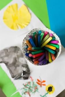 幼稚な絵と白い鍋に明るい色とりどりのペンのセットの上面図