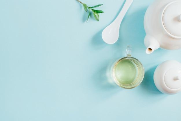 青い表面にお茶とお茶の道具、砂糖のボウルとカップのセットの上面図