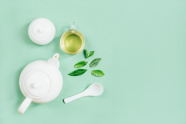 緑の表面にお茶とお茶の道具、砂糖のボウルとカップのセットの上面図