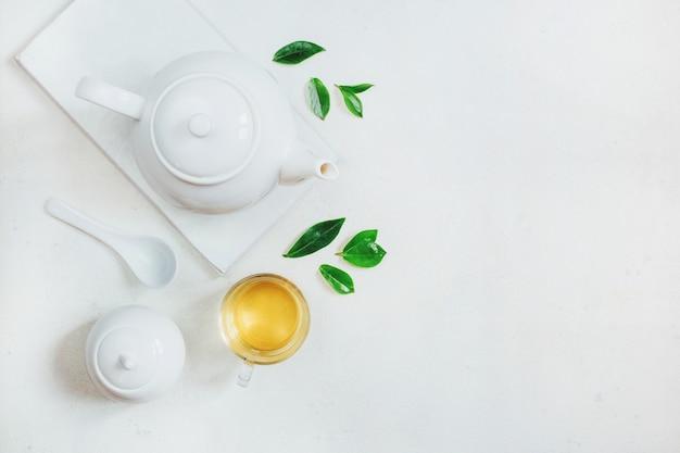 茶器、砂糖入れ、白い表面にお茶とカップのセットの上面図