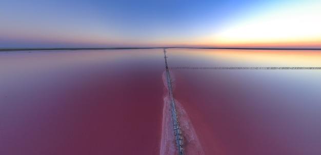 Вид сверху на блестящее соленое розовое озеро и тропу по нему