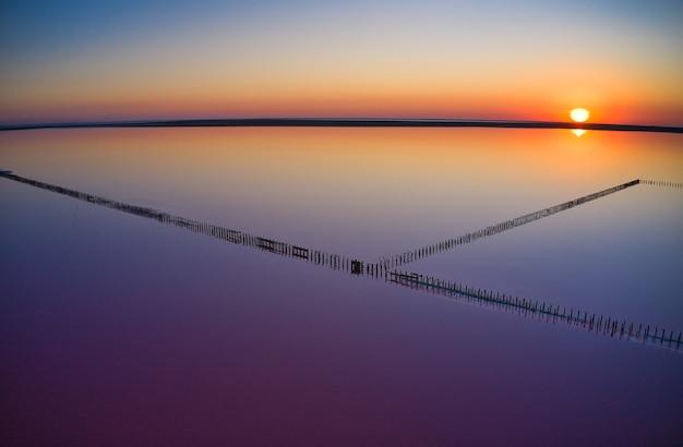 반짝이는 짠 분홍색 호수와 그것을 따라 경로의 상위 뷰