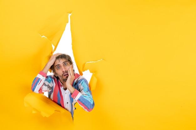 黄色い紙の破れた穴を通して何かを見ているショックを受けた若い男の上面図