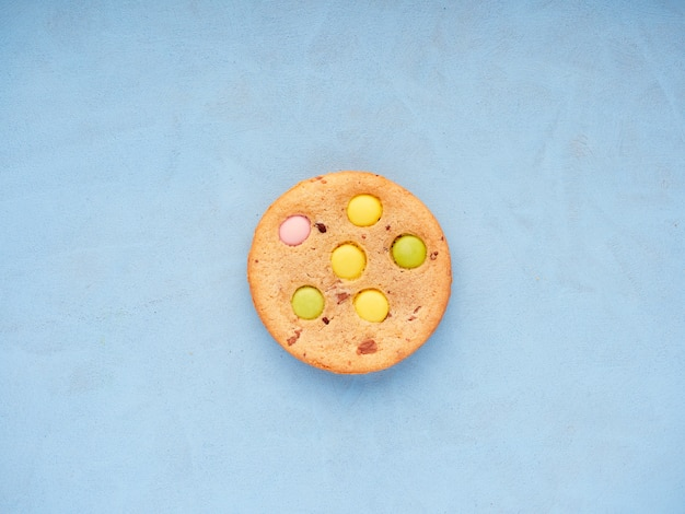 Вид сверху одного печенья с цветной конфетой, встроенной поверх синей поверхности