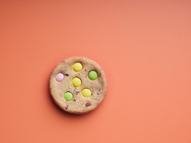 Вид сверху одного печенья с цветной конфетой, встроенной поверх оранжевой поверхности
