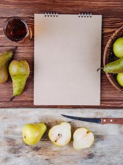 木製の背景にスケッチブックと梨ジュースのグラスと新鮮な熟した梨の平面図
