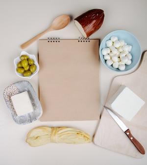 白いテーブルにスケッチブックとブルーボウル、フェタチーズ、スモーク、文字列のチーズのチーズミニモッツァレラチーズの様々なタイプの上面ビューとオリーブのピクルス