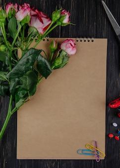 暗い背景の木の上に横たわる芽とピンク色のバラとスケッチブックのトップビュー