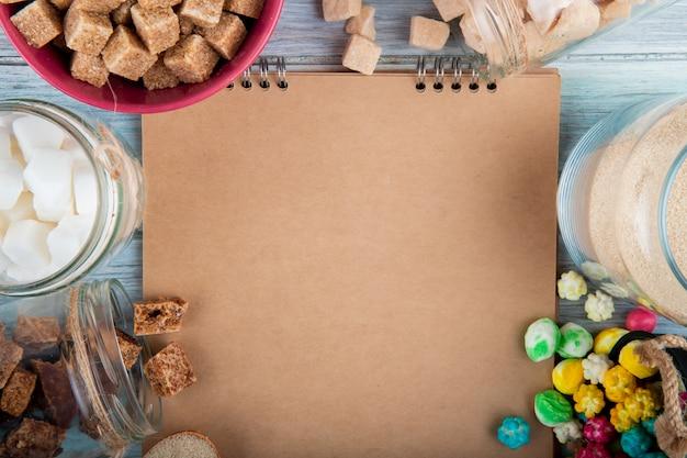 Вид сверху альбом с различными видами сахара и конфет в мисках и стеклянных банках, расположенных вокруг на деревенском фоне