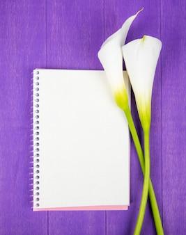 보라색 나무 배경에 고립 된 흰색 칼라 백합과 스케치 북의 상위 뷰