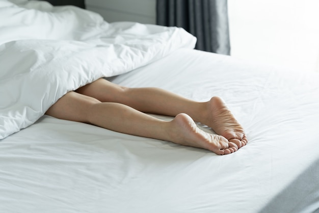 スリムな女性の足の平面図です。自宅で彼女のベッドで寝ている若い女性の裸の足。