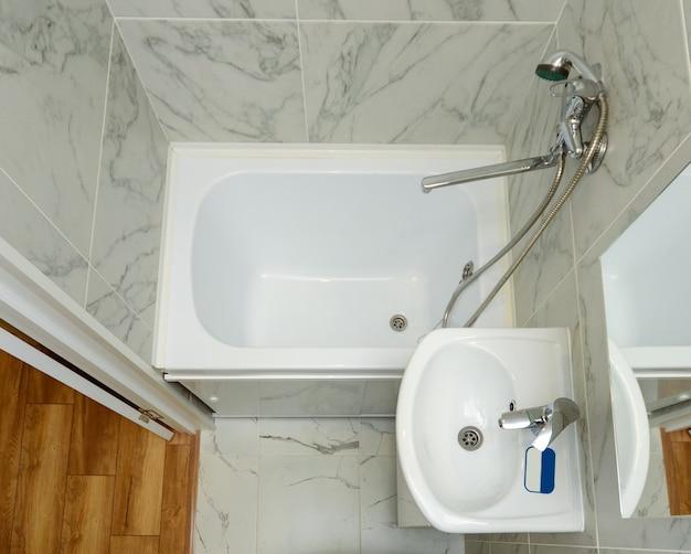 小さな白いバスルームの上面図。小さなアパートのバスルームの例。