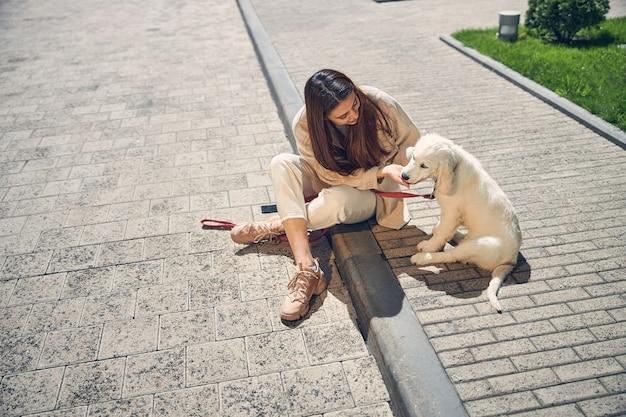 彼女の4本足の友人のあごをなでる笑顔の長い髪の若い雌犬の飼い主の上面図