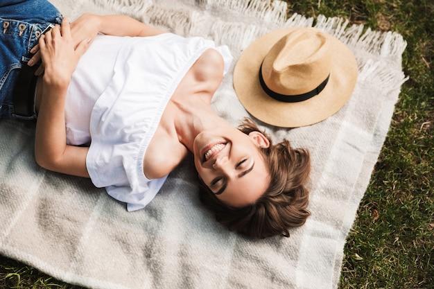 毛布の上に横たわっている笑顔の少女の上面図