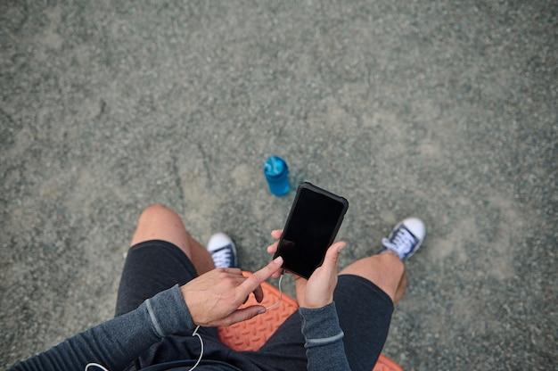 휴대 전화를 들고 복사 공간이 있는 검은색 빈 화면에 손가락을 가리키는 스포츠맨의 상위 뷰. 심장 박동을 확인하는 모바일 애플리케이션에서 운동하는 선수