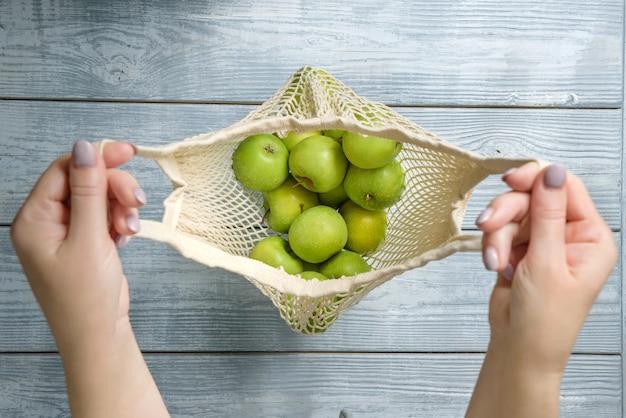 女性の手にリンゴが入ったストリングバッグの上面図。木製のテーブルの背景にリンゴとオープンバッグ。セレクティブフォーカスの構成。
