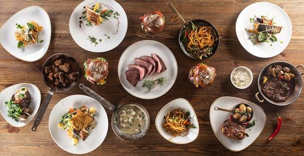 접시에 제공되는 채식주의자와 육식가를 위한 다양한 식사로 가득 찬 테이블의 위쪽 전망