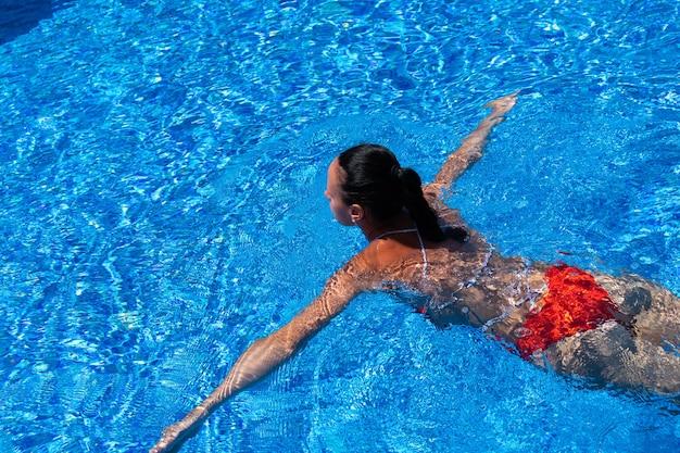 日焼けした女の子、女性、赤い水着のモデル、プールの青い水で泳いでいる上面図。