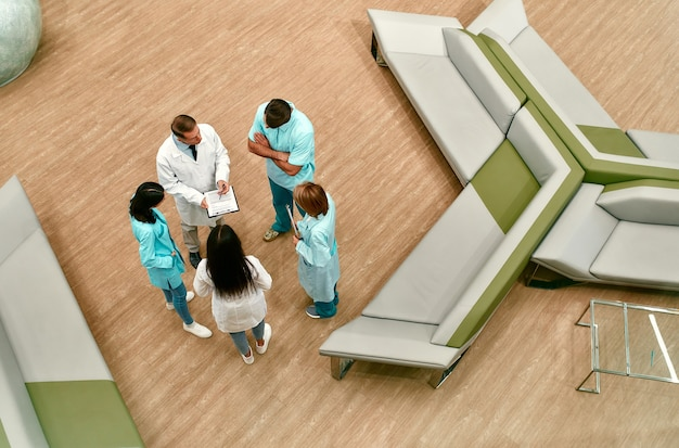 Вид сверху на команду врачей, которые стоят в холле современной клиники и обсуждают методы лечения пациентов.