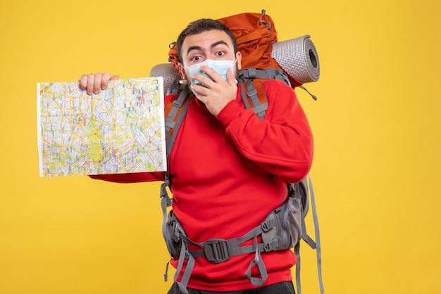 黄色の背景に地図を持ったバックパックで医療用マスクを着た旅行者の男のトップビュー