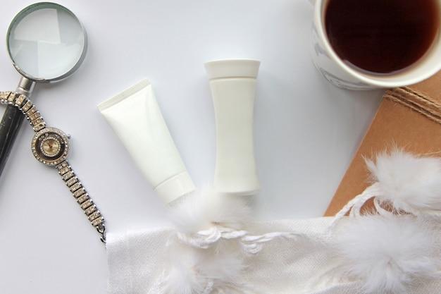 Вид сверху тюбик крема с лосьоном и часами с лупой и чашкой чая на столе
