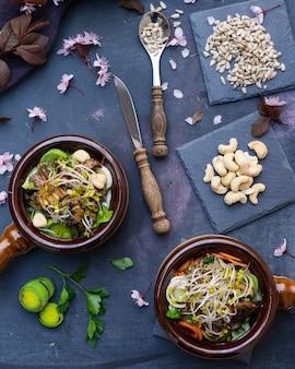 Вид сверху веганской еды с грибами, луком, морковью и луком-пореем