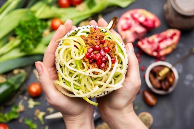 컵에 나선형 호박, 토마토 소스, 석류가 들어간 비건 채식 식사의 상위 뷰