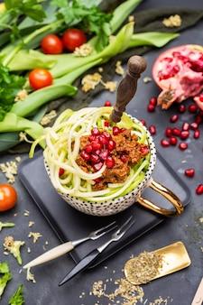 Вид сверху веганской еды со спиральными кабачками, томатным соусом и гранатами в чашке