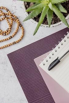Взгляд сверху фиолетовой циновки йоги, плохие деревянные шарики на белой поверхности. основные аксессуары для практики йоги и медитации. копировать пространство