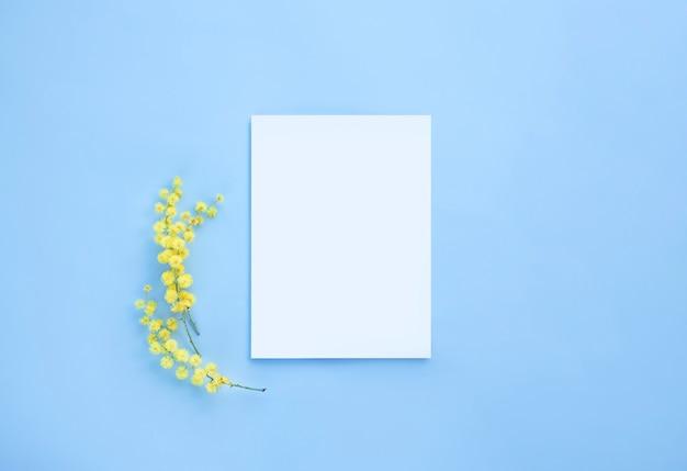 ミモザの花と白いカードのモックアップの上面図