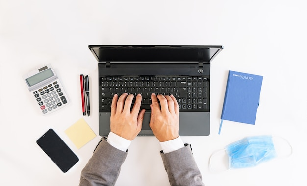 Covid19コロナウイルスの大流行により、ラップトップ、計算機、携帯電話、ポストイット、ペン、ジャーナル、フェイスマスクにビジネスワーカーが書いている白いオフィステーブルの上面図