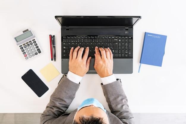 Covid19 전염병으로 인해 얼굴에 마스크가 달린 노트북에 쓰는 비즈니스 작업자가있는 흰색 사무실 테이블의 상위 뷰이며 계산기, 휴대 전화, 게시, 펜, noteboo가 있습니다.