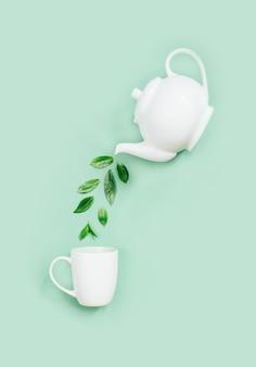 薄緑色の表面の白いカップに茶葉を注ぐ白いティーポットの上面図