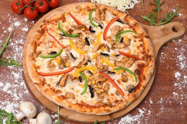 Вид сверху целой пиццы со сладким перцем, кукурузой, мясом и грибами на столе