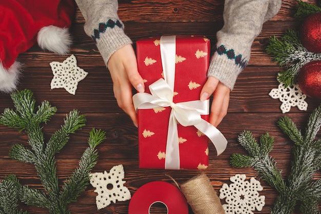 Вид сверху руки женщины с рождественским подарком на деревянном фоне