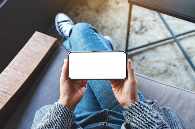 Вид сверху женщины, держащей черный мобильный телефон с пустым белым экраном рабочего стола