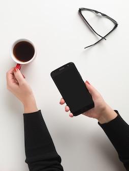 Взгляд сверху женщины держа красную чашку кофе с одной рукой и сотовым телефоном
