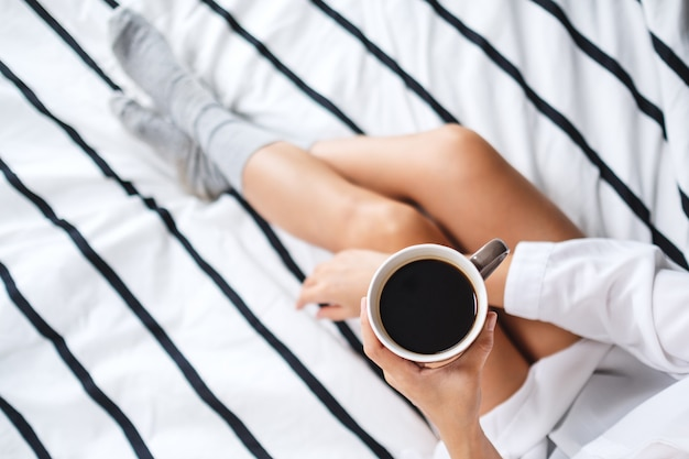Взгляд сверху женщины держа и выпивая горячий кофе в белой уютной кровати дома утром