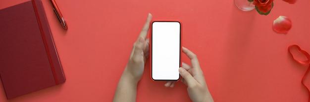 Взгляд сверху женщины держа smartphone пустого экрана пока сидящ на творческом рабочем пространстве