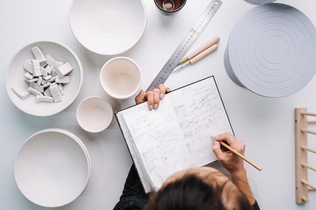 새로 생성 된 빈 식기가있는 테이블 옆에 그녀의 시간표에 메모를 작성하는 여자의 상위 뷰