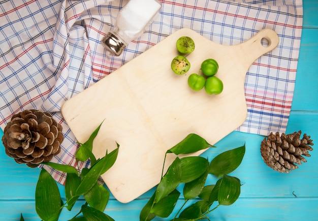 木の板と青い木製テーブルの格子縞の生地にコーンと散乱のサワーグリーンプラムの平面図